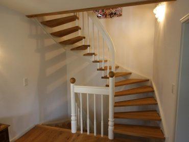 Handlauftragende Systemtreppe in Eiche mit rund verleimten Handlauf und weiß lackierter Wandwange.