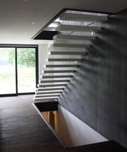 Kragarmtreppe EGO in deckend weiß lackiert an Sichtbetonwand.
