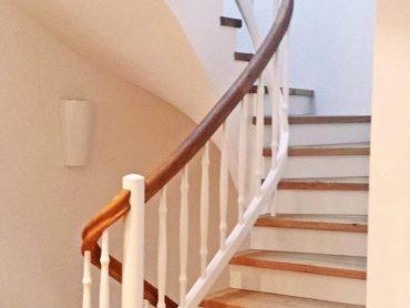 Stufen auf Beton in Eiche mit Setzstufen in weiß. Geländer mit leicht gedrechselten Sprossen. Pfosten, Sprossen und Untergurt weiß lackiert. Geländer rund verlaufend.