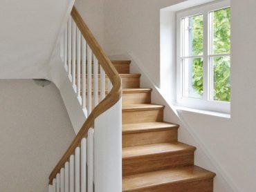 Klassische geschlossene gestemmte Wangentreppe in Eiche mit Griffprofil und profilierten Stufenkanten. Wangen und Geländerteile weiß lackiert