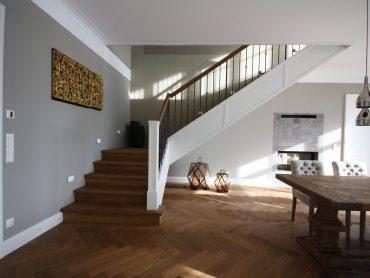 Gestemmte Wangentreppe im klassischen Stil. Wangen weiß lackiert. Stufen und Setzstufen Eiche angeräuchert. Geländerstäbe Stahl leicht geschmiedet.