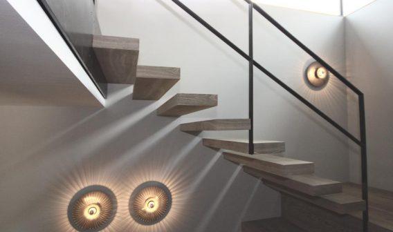 Kragarmtreppe mit Sitzmöbel bis Podest sowie Treppenmöbel. Eiche Sonderfarbton. Geländer als Flachstahlgeländer in Rohstahl.
